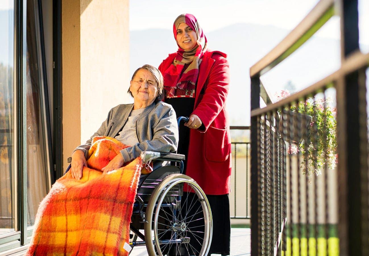 female caregiver assisting senior woman on wheelchair