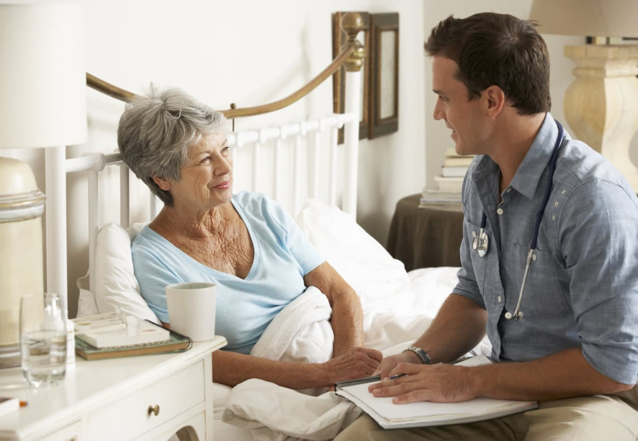 doctor talking with senior female patient in bed at home