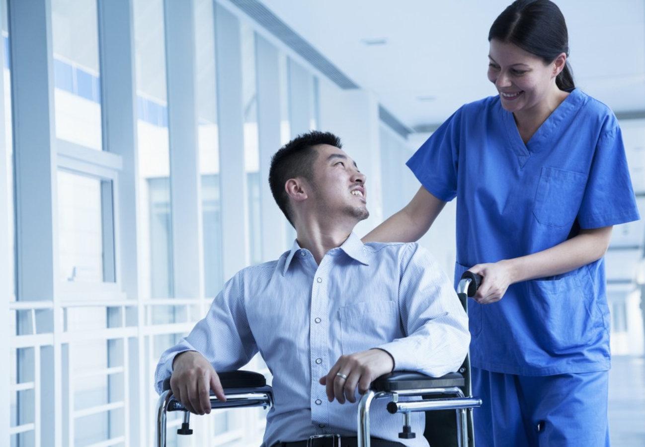 female caregiver assisting a man on a wheelchair